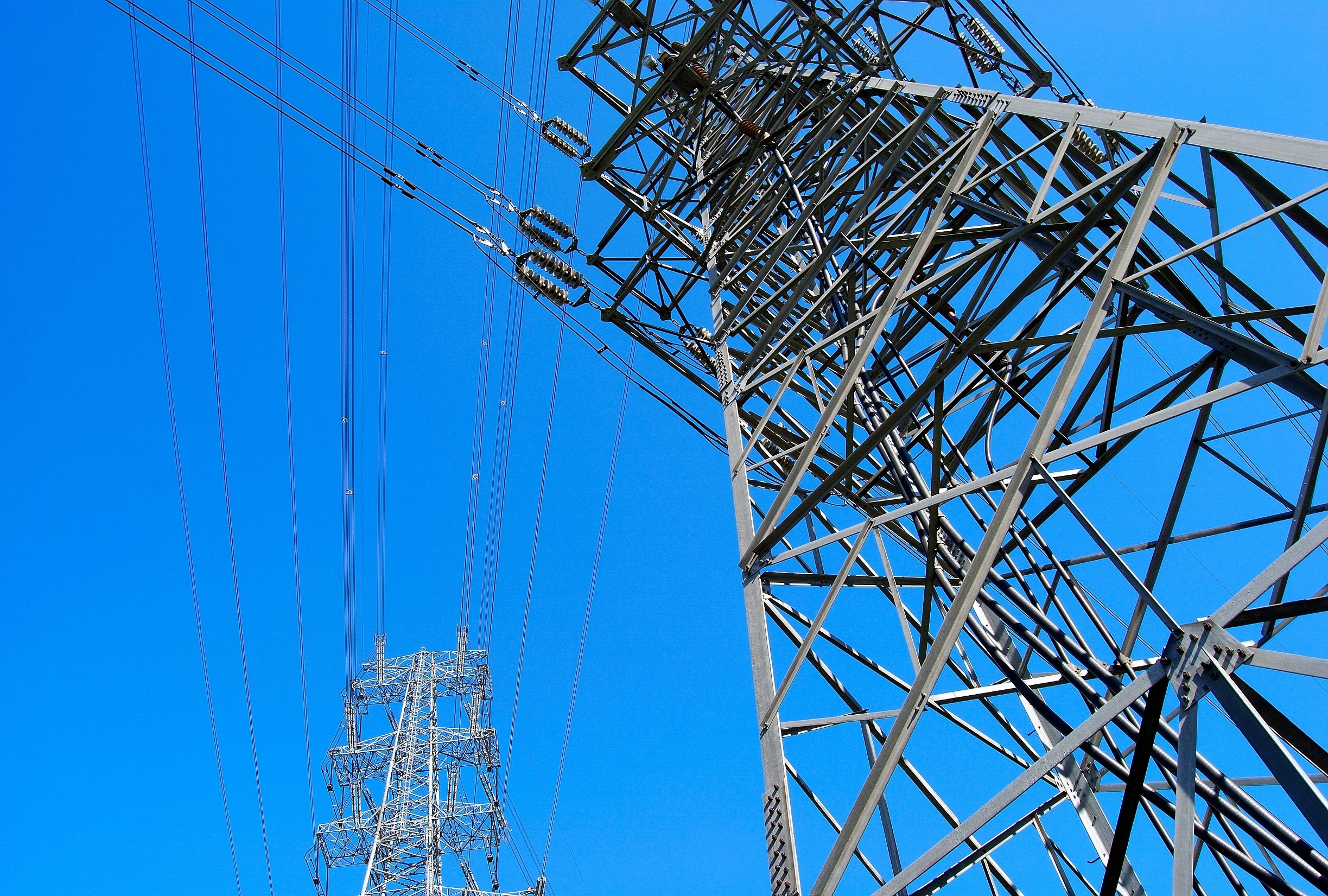 electricity pylons with lines crossing in the sky
