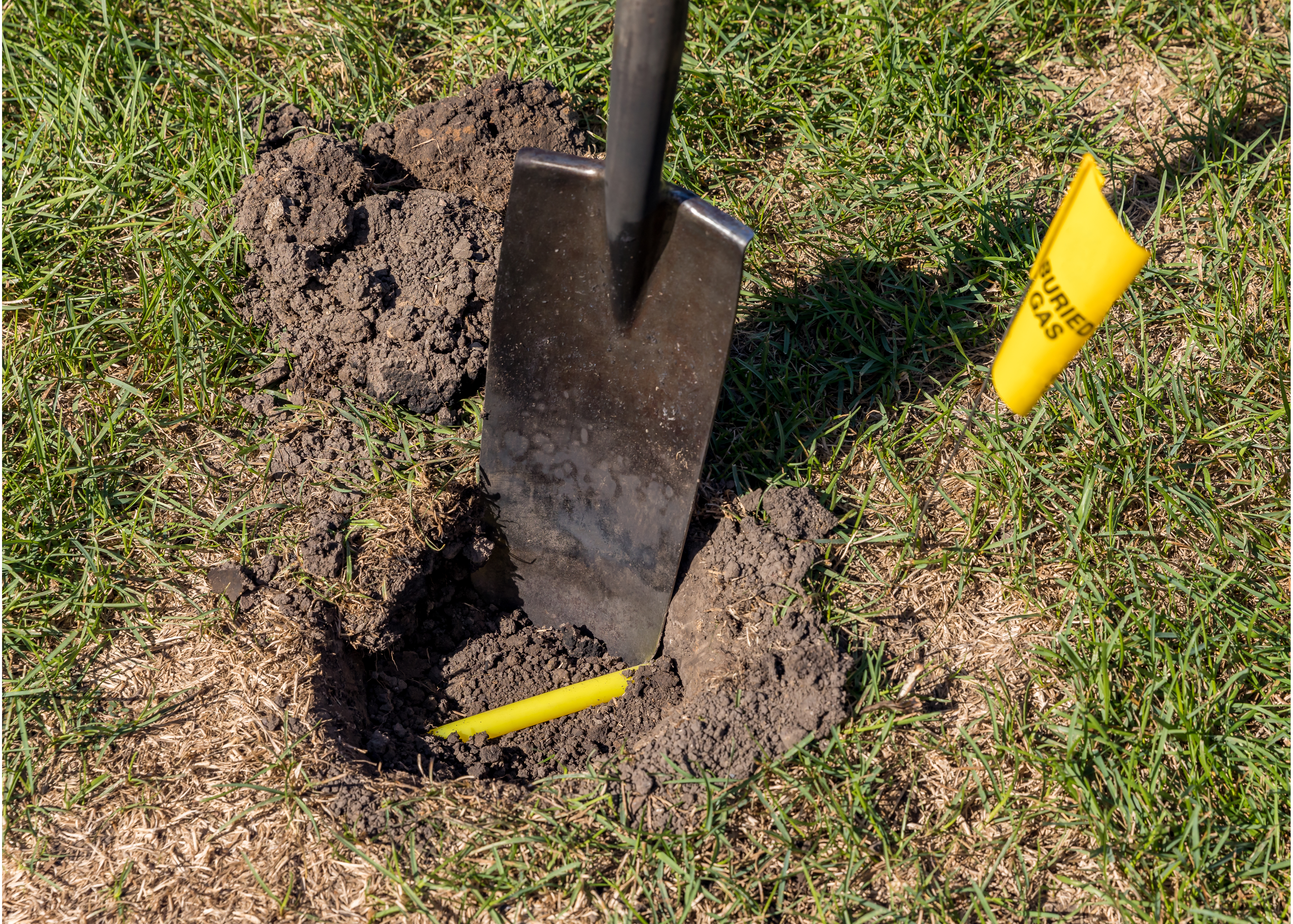 Hole in yard with yellow plastic natural gas utility lines buried in ground, shovel and with natural gas warning flag