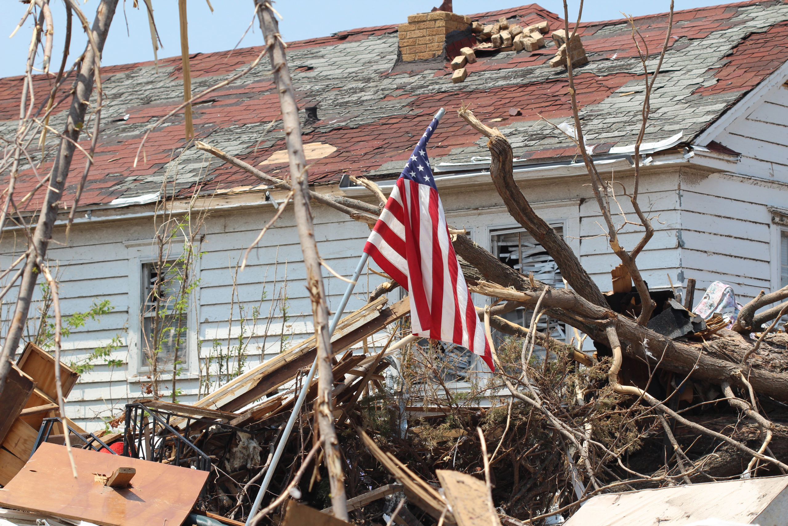 american flag in fallen trees from a storm